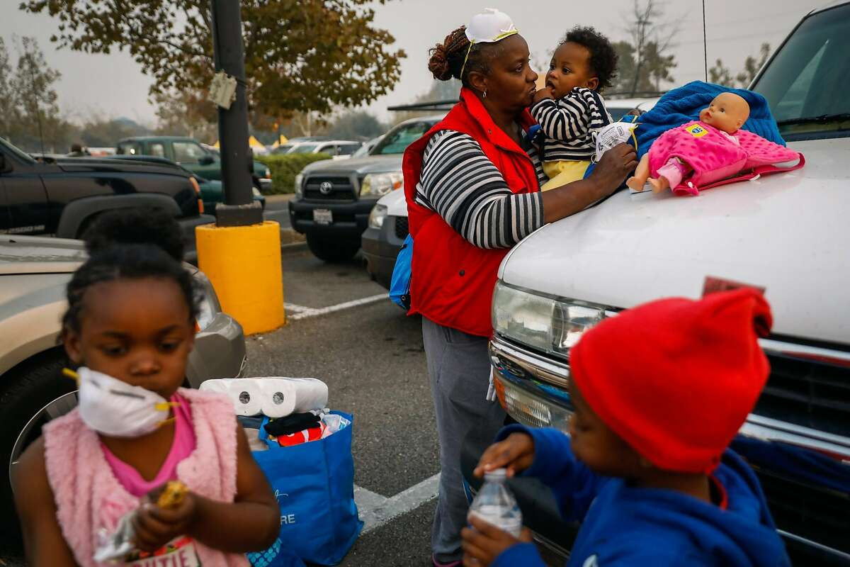 Wednesday, Nov. 14, 2018: In the smoke-filled parking lot of an emergency evacuation center in Chico, Calif., Dottie Flanders (center) holds her 9-month-old grandson, Isaiah Brooks, while her other grandchildren, London Mayo, 4 (left), and Messiha Mayo, 3, stand nearby. The family was picking up supplies after the children and their mother had to flee the Camp Fire, which destroyed most of the town where they lived, neighboring Paradise, Calif. Photo: Gabrielle Lurie