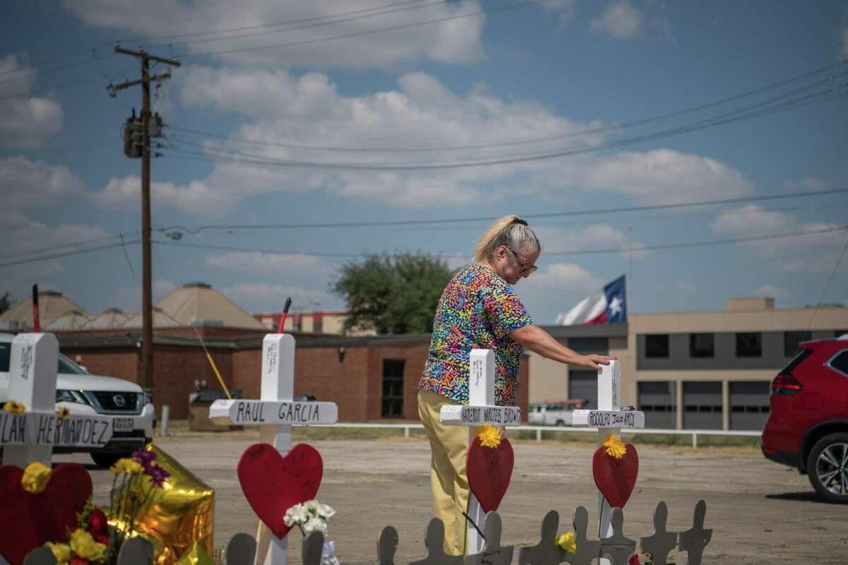 An Odessa resident pays her respects at a makeshift memorial created in memory of the victims killed in a recent mass shooting in Odessa, Texas, Sept. 3, 2019.