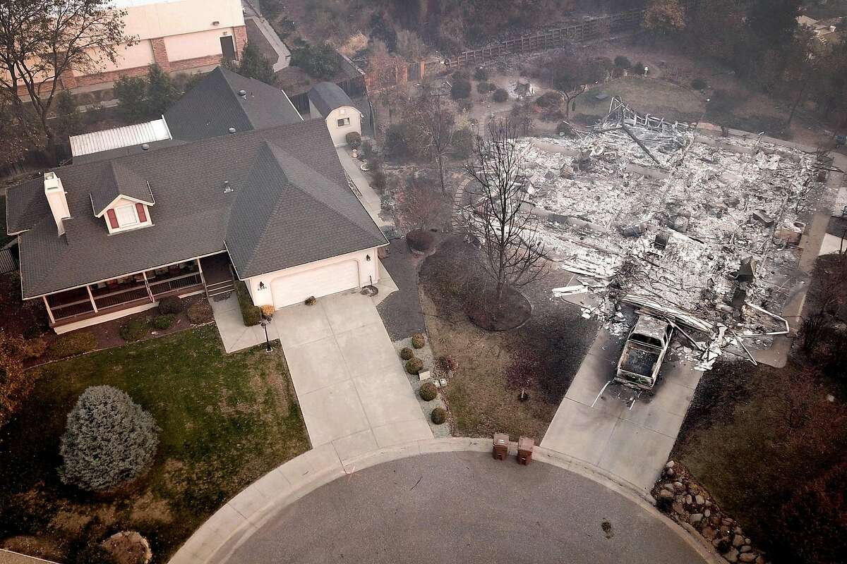 Thursday, Nov. 15, 2018: A home left intact and another turned to ash by the Camp Fire are seen side by side at the end of a cul de sac in the town of Paradise. The worst wildfire in state history would destroy more than 13,000 homes in Paradise and surrounding Butte County. Photo: Santiago Mejia