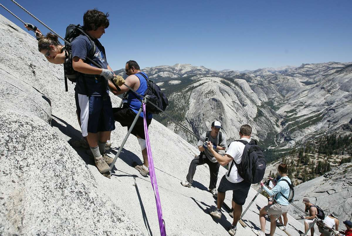 Climbers on the cable section of Yosemite's Half Dome rest during their climb in this 2007 file photo, before the park instituted a permit system for climbing the dome.