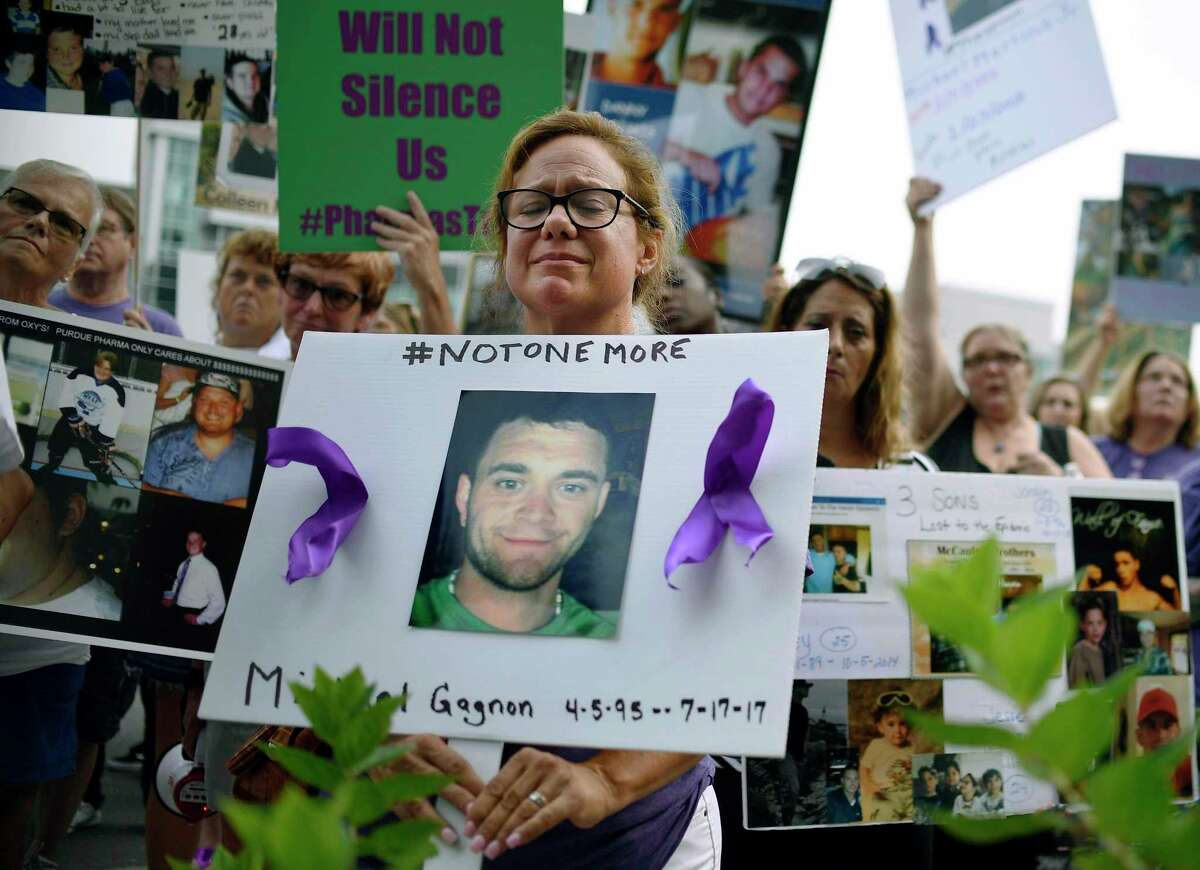 In this August 2018 file photo, protesters who have lost family members and friends to opioid overdoses demonstrate outside the downtown Stamford headquarters of OxyContin Purdue Pharma. The company is reportedly negotiating a possible end to U.S. Department of Justice investigations.