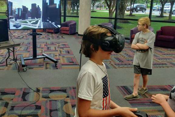 A Lone Star College-Tomball Community Library patron tries out a virtual reality headset.