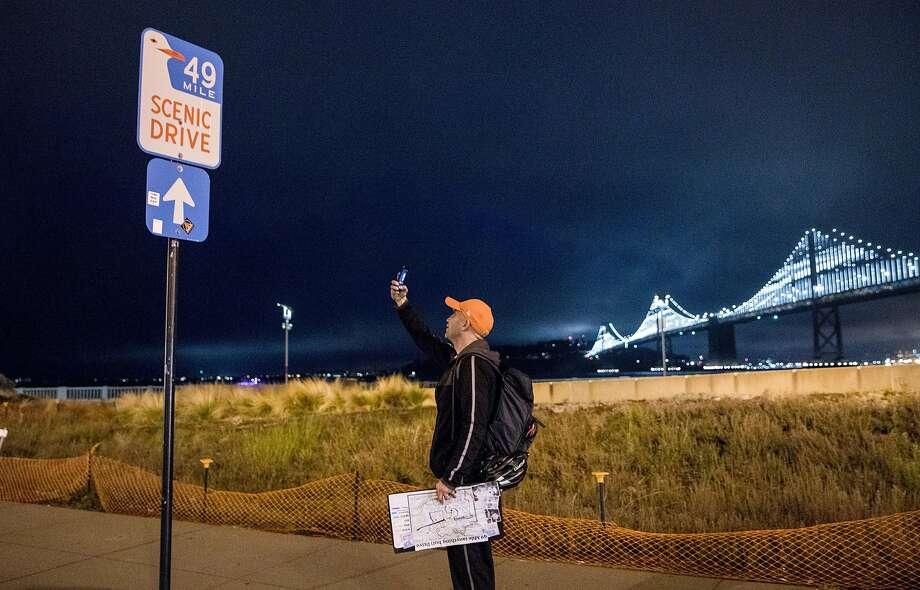 San Francisco Chronicle reporter Peter Hartlaub takes a picture of the 49-Mile Scenic Drive marker along the Embarcadero in S.F. as he and fellow reporter Heather Knight attempt to traverse the 49-Mile Scenic Drive without using a car. Photo: Jessica Christian / The Chronicle