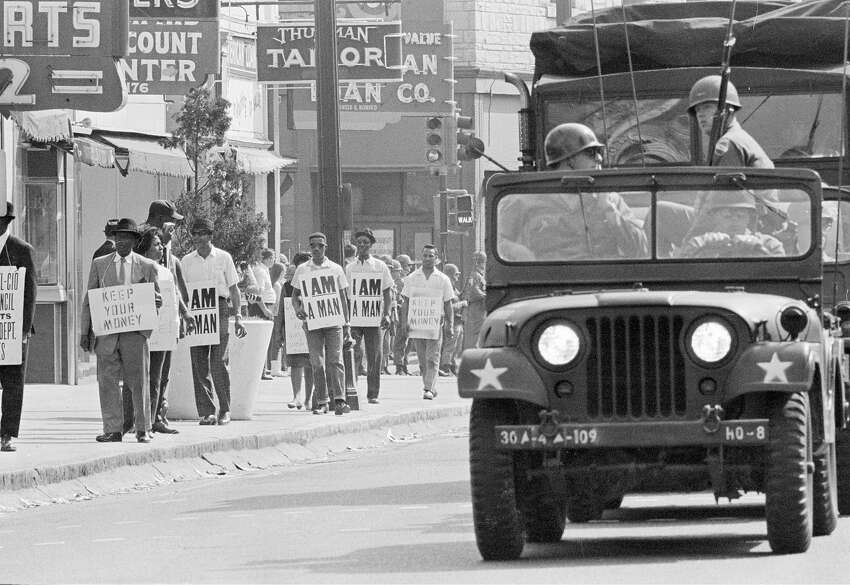 FILE - In this March 30, 1968 file photo, Tennessee National Guard troopers in jeeps and trucks escort a protest march by striking Memphis sanitation workers through downtown Memphis, Tenn. A prominent member of the Memphis, Tenn., sanitation workers union whose historic strike drew the Rev. Martin Luther King Jr. to the city where he was assassinated has died, close friends said Tuesday, Aug. 27, 2019. Baxter Leach died at age 79 on Tuesday morning after battling cancer. (AP Photo, File)