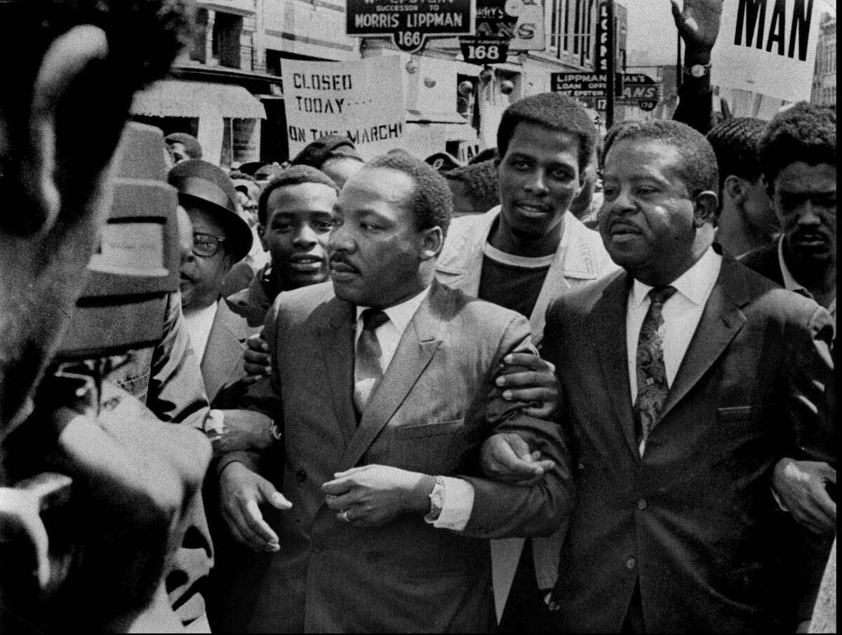 ADVANCE FOR SUNDAY, MARCH 29--FILE--Dr. Martin Luther King Jr. and Rev. Ralph Abernathy, right, lead a march on behalf of striking Memphis sanitation workers March 28, 1968. The dignity of the march soon gave way to disorder as a group of about 200 youths began breaking windows and looting. King agonized over what had happened. Within a week, King was dead, killed by an assassin's bullet at Memphis' Lorraine Motel. (AP Photo/Sam Melhorn, The Commercial Appeal)