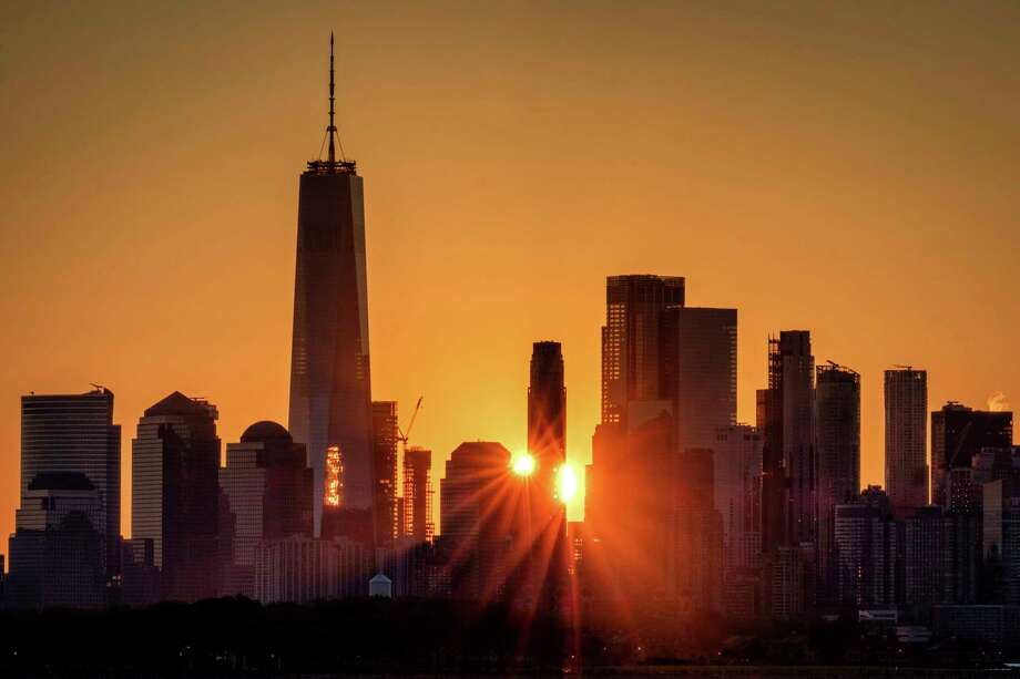 FILE - In this July 1, 2019, file photo the sunlight flares around the buildings in lower Manhattan as the sun rises in New York. Despite a decade-plus of economic growth, Americans have slowed the pace at which theya€™re forming new companies, a trend that risks further widening the gap between the most affluent and everyone else. (AP Photo/J. David Ake, File) Photo: J. David Ake / Copyright 2019 The Associated Press. All rights reserved.