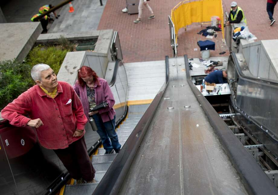 Riders make their way up an escalator as another is being repaired at the Powell Street BART Station. Photo: Photos By Jessica Christian / The Chronicle