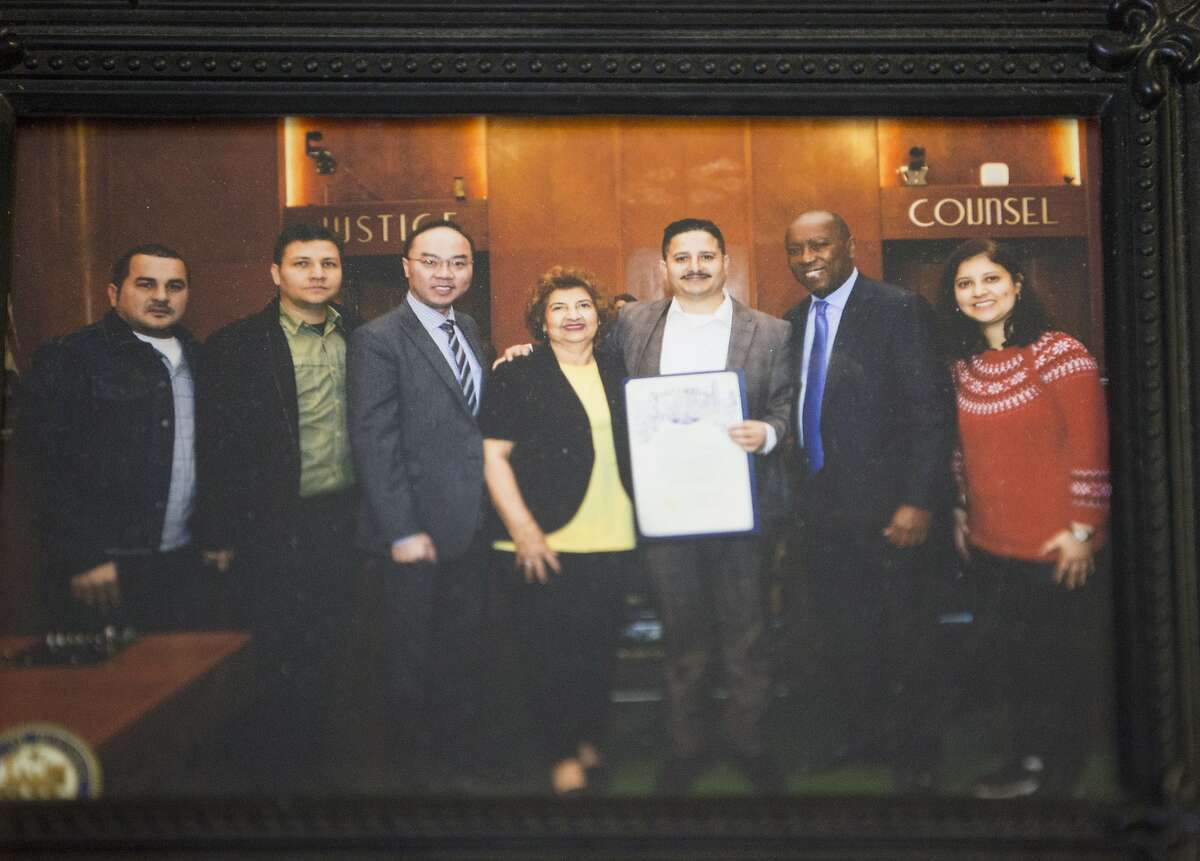 A photograph of Roland Gramajo holding a proclamation from Mayor Sylvester Turner in 2018 is displayed on the wall at Gramajo's business office on Friday, Sept. 6, 2019, in Houston. The 40-year-old was arrested by U.S. Immigration and Customs Enforcement while going to work on Thursday. Gramajo, a Guatemala native, has five U.S. citizen children and a legal resident wife.