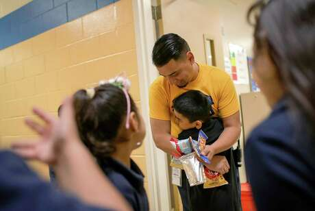 Alejandro Martinez, a wraparound resource coordinator at Sanchez Elementary School, hugs Nathan Ayala, 7, on his birthday after giving him a snack. The wraparound program is a welcomed effort to help HISD students face challenges outside the classroom.