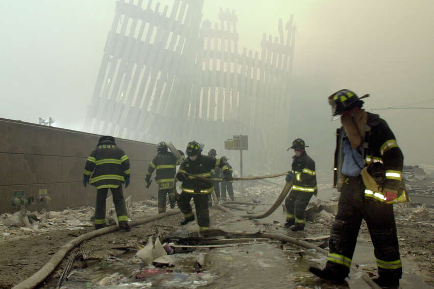 FILE - In this Sept. 11, 2001 file photo, firefighters work beneath the destroyed mullions, the vertical struts which once faced the outer walls of the World Trade Center towers, after a terrorist attack on the twin towers in New York. New research released on Friday, Sept. 6, 2019 suggests firefighters who arrived early or spent more time at the World Trade Center site after the 9/11 attacks seem to have a greater risk of developing heart problems than those who came later and stayed less. (AP Photo/Mark Lennihan)