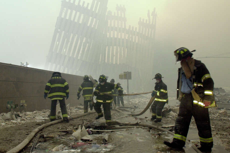 FILE - In this Sept. 11, 2001 file photo, firefighters work beneath the destroyed mullions, the vertical struts which once faced the outer walls of the World Trade Center towers, after a terrorist attack on the twin towers in New York. New research released on Friday, Sept. 6, 2019 suggests firefighters who arrived early or spent more time at the World Trade Center site after the 9/11 attacks seem to have a greater risk of developing heart problems than those who came later and stayed less. (AP Photo/Mark Lennihan) Photo: Mark Lennihan / Copyright 2019 The Associated Press. All rights reserved.