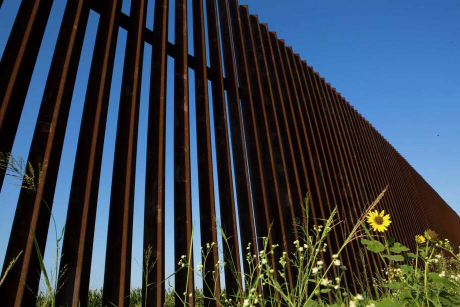 The rust-colored steel U.S-Mexico border fence stands by the border in Brownsville, Texas. A newer version of the fence is set to be built next year though the middle of the River Bend Resort and Golf Club, leaving about 70 percent of residents on the south side of the barrier. Photo: Marie D. De Jesus, MBI / Associated Press / Houston Chronicle