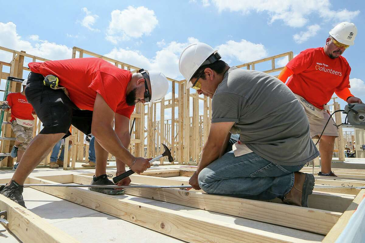 Habitat for Humanity volunteers Martin Gatica, from left, Robert Chavarria and Arnulfo Aguilar, from Wells Fargo, attach a metal brace to a wall frame before raising it while building a new home in the Lenwood Heights subdivision on Friday, Sept. 6, 2019. The nonprofit is building 10 homes expected to be ready before the holidays.