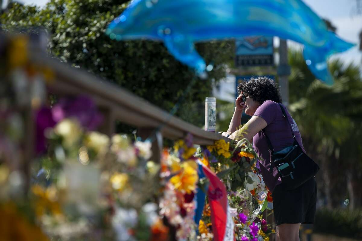 A woman gets emotional after placing flowers at a memorial for the victims of the Conception in the Santa Barbara Harbor on Wednesday, Sept. 4, 2019 in Santa Barbara, Calif. A fire raged through the boat leaving 34 people dead. (AP Photo/Christian Monterrosa)