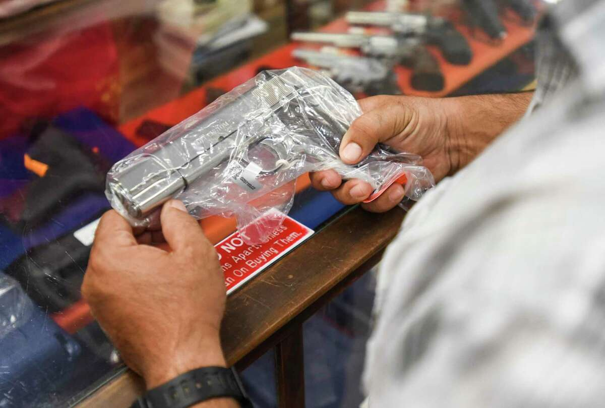 A customer handles a handgun they are looking to purchase at JJ's Pawn Shop Friday afternoon. Photo taken on Friday, 09/06/19. Ryan Welch/The Enterprise