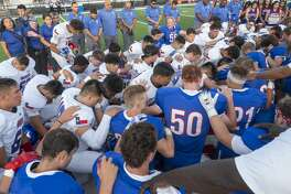 Midland Christian players and coaches come together with El Paso Americas' players and coaches at the 50 yard line 09/06/19 before the game at Gordon Awtry Stadium for a prayer for victims from both cities from recent shooting tragedies. Tim Fischer/Reporter-Telegram