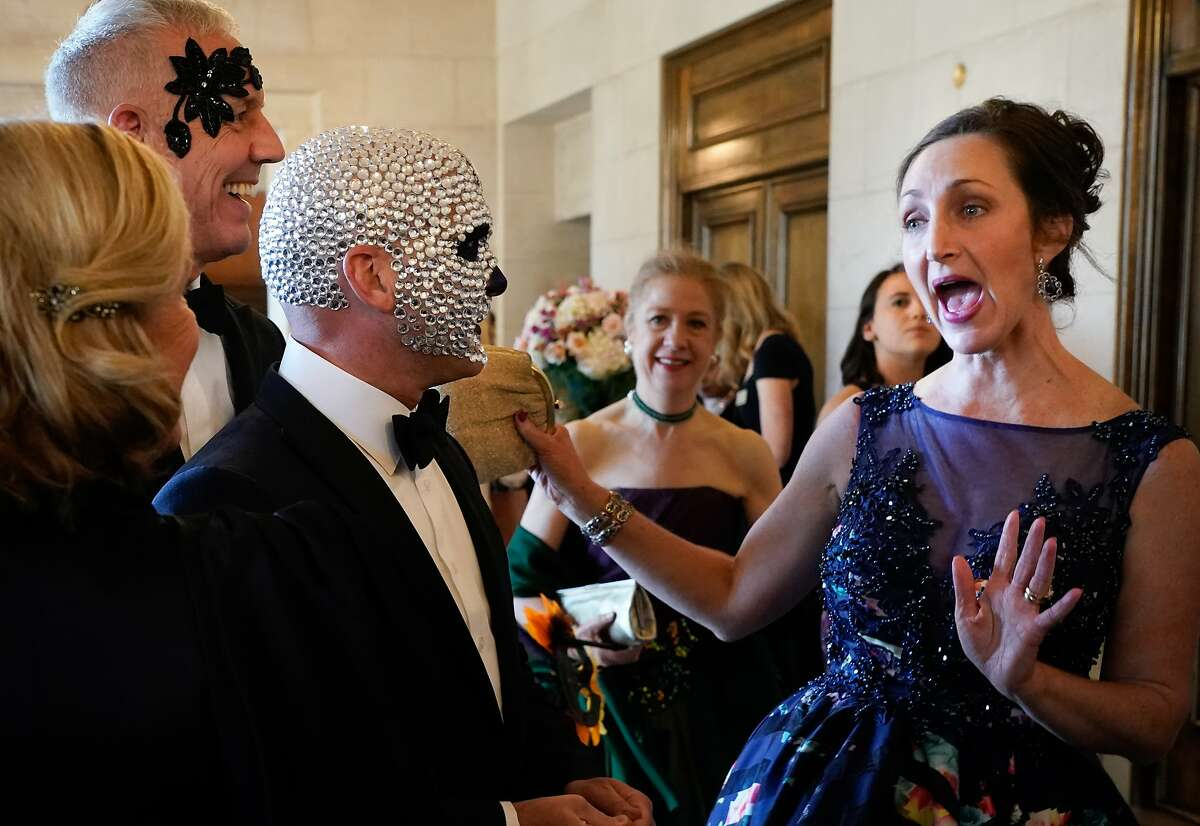 Ronnie Genotti (middle) and David Oldroyd (left) are greeted by Alison Morr Gemperle at the start of the 2019 Opera Ball on Friday in San Francisco.