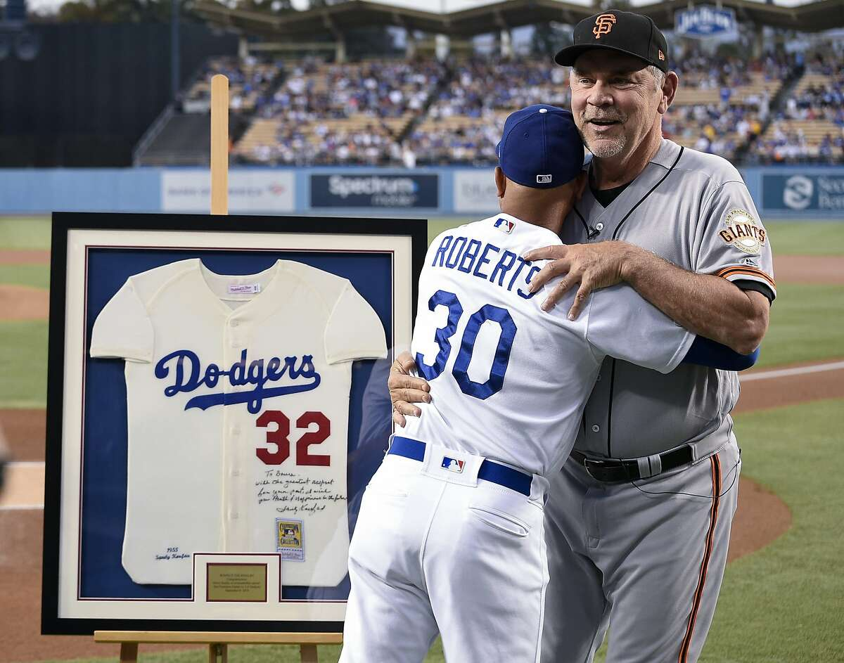 San Francisco Giants manager Bruce Bochy, right, hugs Los Angeles Dodgers manager Dave Roberts after being given a signed Sandy Koufax jersey to commemorate his last series with the Giants at Dodger Stadium, in Los Angeles, Friday, Sept. 6, 2019. (AP Photo/Kelvin Kuo)