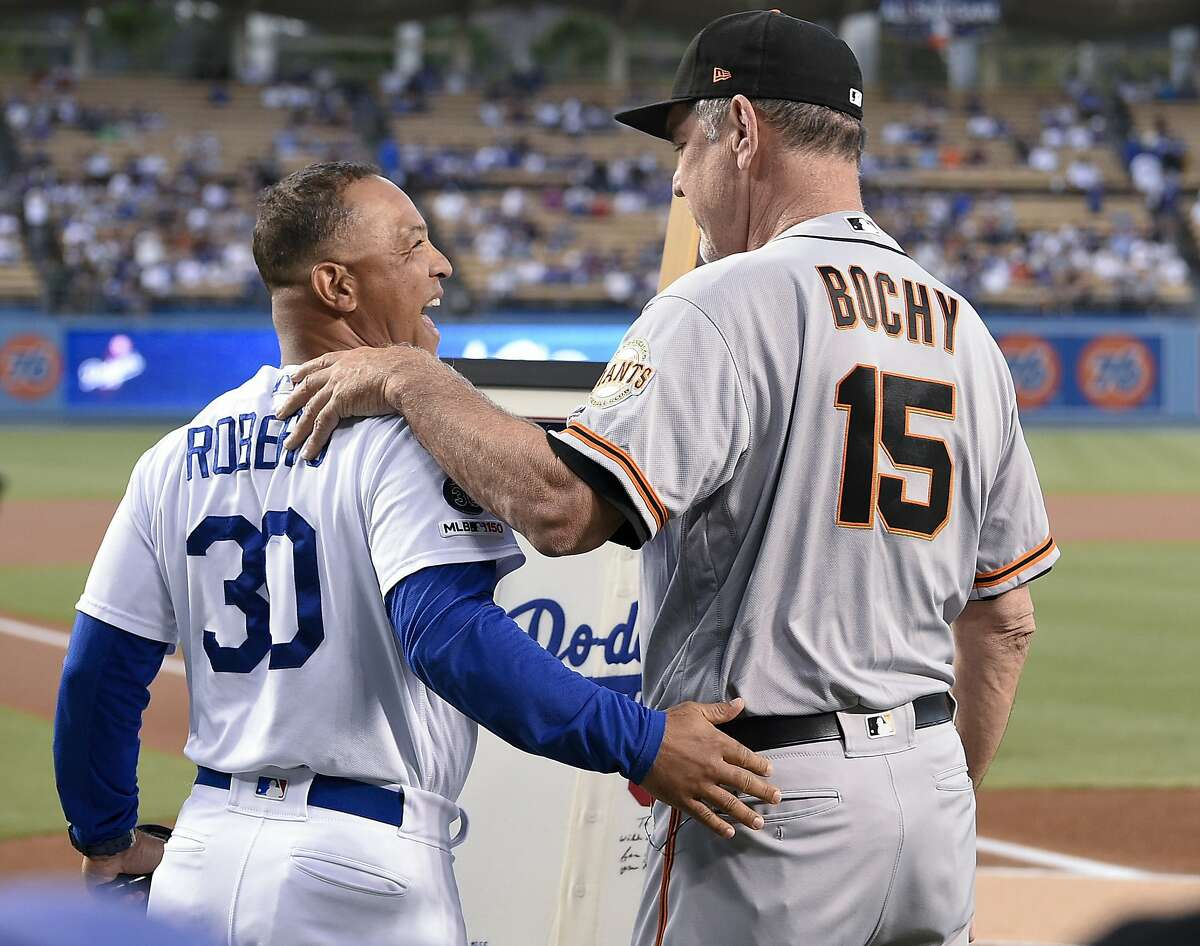 San Francisco Giants manager Bruce Bochy, right, embraces Los Angeles Dodgers manager Dave Roberts after being given a signed Sandy Koufax jersey to commemorate his last series with the Giants at Dodger Stadium, in Los Angeles, Friday, Sept. 6, 2019. (AP Photo/Kelvin Kuo)