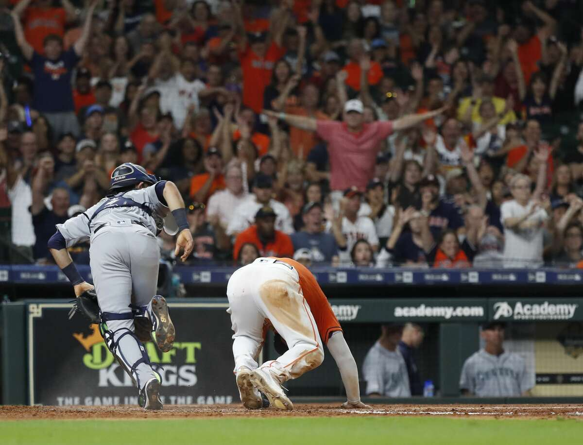 Fans signal that Houston Astros Alex Bregman (2) is safe as he stole home against Seattle Mariners catcher Austin Nola (23) during the fifth inning of an MLB baseball game at Minute Maid Park, Friday, Sept. 6, 2019, in Houston.