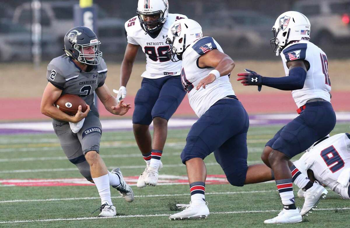 Boerne Champion quarterback Luke Boyers (2) evades Veterans Memorial defenders and turned a seemingly dead play into a long yardage touchdown in the first quarter of their game in Boerne on Friday, Sept. 6, 2019.
