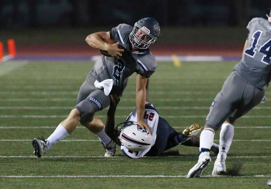 Boerne Champion quarterback Luke Boyers (02) fends off a tackle by Samarie Stevenson (24) during their game in Boerne on Friday, Sept. 6, 2019. (Kin Man Hui/San Antonio Express-News) Photo: Kin Man Hui, Staff / Staff Photographer / ©2019 San Antonio Express-News