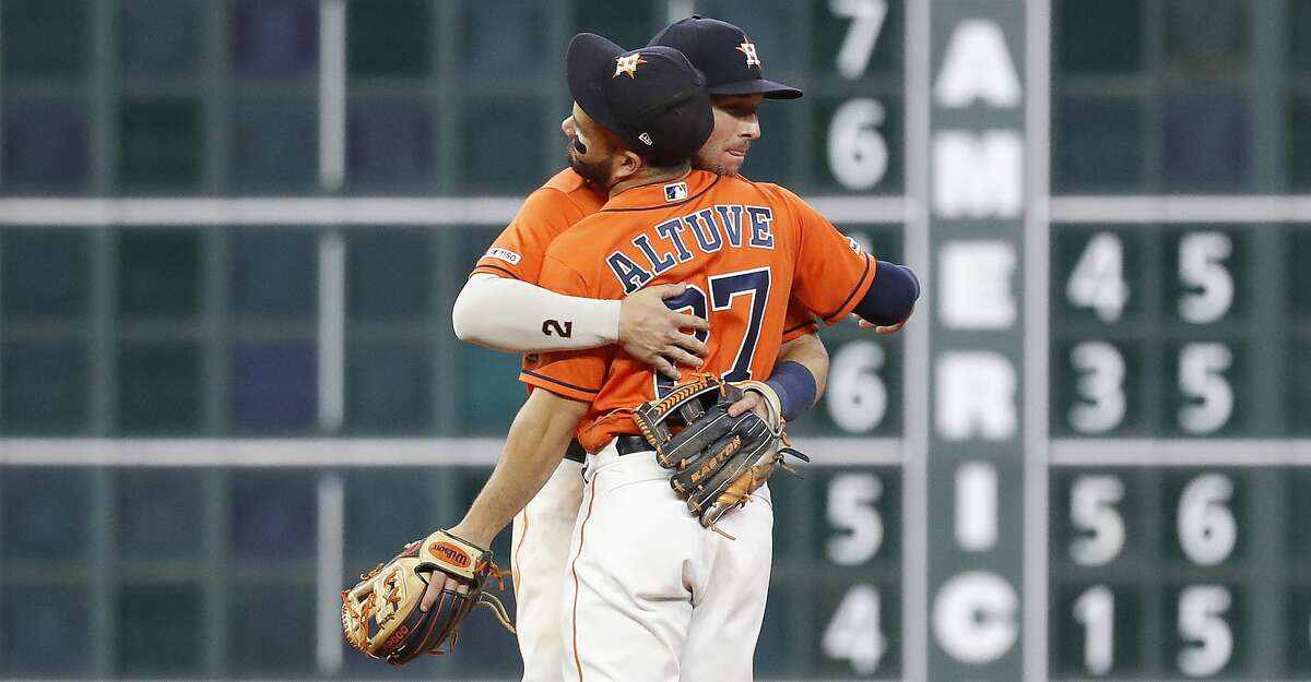 Houston Astros shortstop Alex Bregman (2) and Houston Astros second baseman Jose Altuve (27) hug after the Astros beat the Seattle Mariners 7-4 during an MLB baseball game at Minute Maid Park, Friday, Sept. 6, 2019, in Houston.