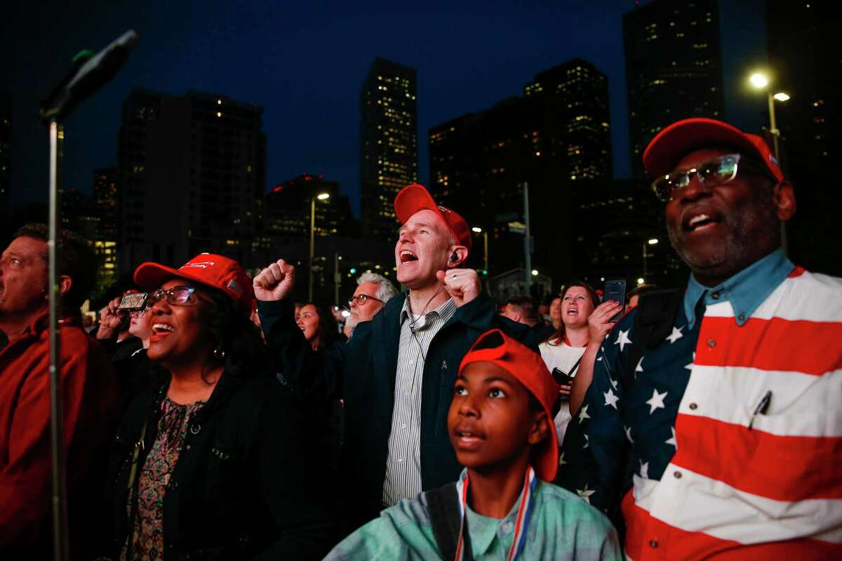 People watch from outside the Toyota Center as President Donald Trump holds a rally with Senator Ted Cruz Monday Oct. 22, 2018 in Houston.