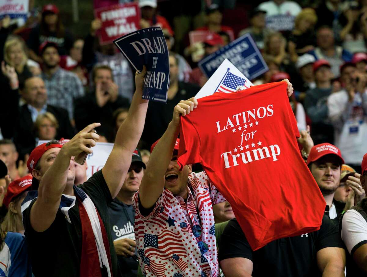 """Supporters of President Donald Trump wave a """"Latinos for Trump"""" T-shirt during a campaign rally for Sen. Ted Cruz (R-Texas) and other Texas Republicans in Houston, Oct. 22, 2018. (Doug Mills/The New York Times)"""
