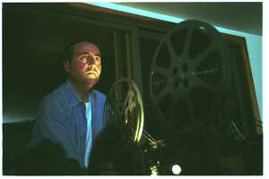 Andy Lehrfeld of Stamford runs the projector at his home in September 2002 at a gathering of the Stamford chapter of the International Laurel & Hardy Appreciation Society.