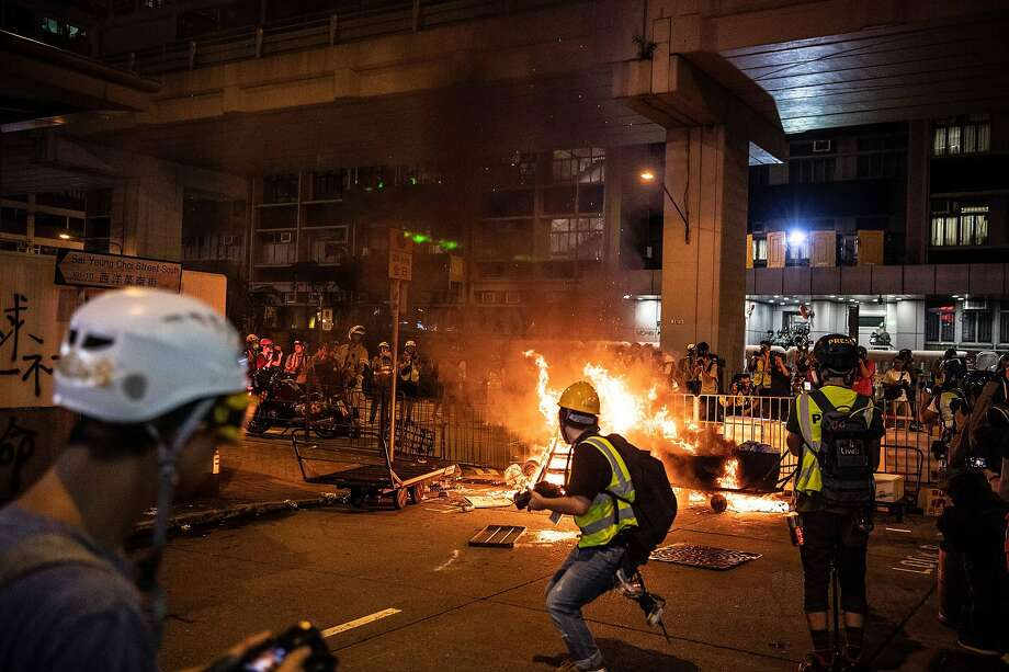 Pro-democracy demonstrators ignite a fire near a police station in Hong Kong. Protesters clashed with officers even after an extradition bill that had inspired the rallies was withdrawn. Photo: Laurel Chor / New York Times