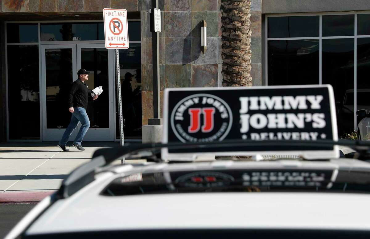 FILE - In this Feb. 6, 2019, photo, Tyler Schwecke, a delivery driver for Jimmy John's, makes a delivery in Las Vegas. Despite pressure from third-party apps, a few big chains continue to use their own drivers, and theya€™re hiring. (AP Photo/John Locher, File)