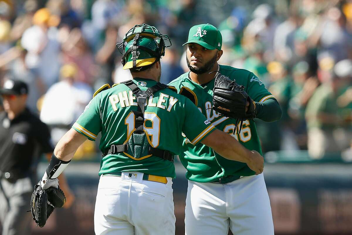 OAKLAND, CALIFORNIA - AUGUST 17: Yusmeiro Petit #36 of the Oakland Athletics celebrates with Josh Phegley #19 after a win against the against the Houston Astros at Ring Central Coliseum on August 17, 2019 in Oakland, California. (Photo by Lachlan Cunningham/Getty Images)