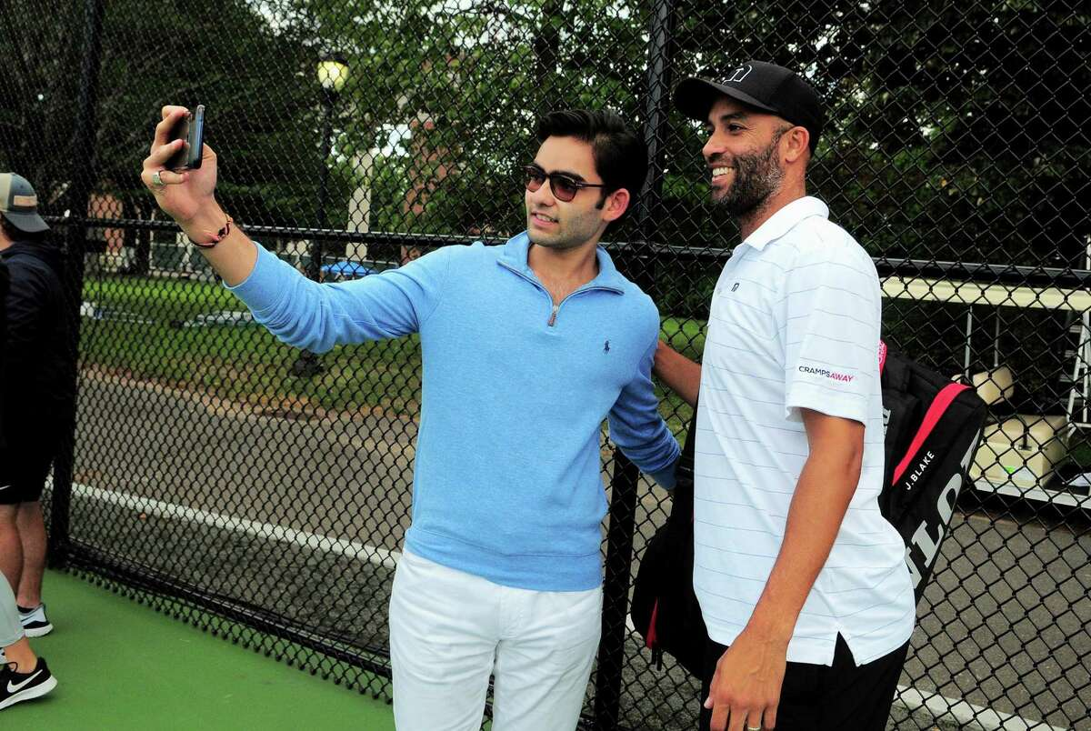 James Blake, right, poses for a selfie with Yale student Yash Bhansali during the Oracle Champions Cup at Yale in New Haven, Conn., on Saturday Sept. 7, 2019. Blake played against Mark Philippoussis as part of the Men's Tennis Legends Series.