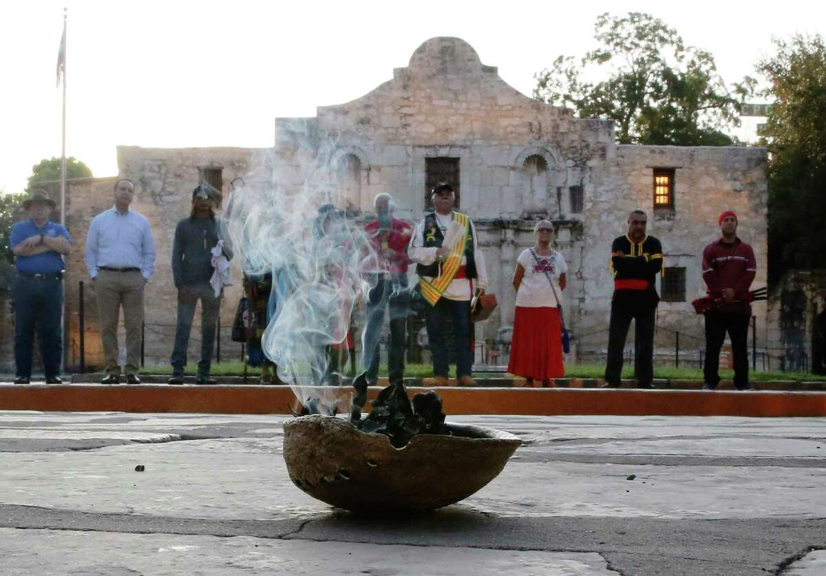 A local Native American group honored buried descendants during their 25th Annual Sunrise Ceremony at the Alamo on Saturday, Sept. 7, 2019. Ramon Juan Vasquez, executive director of American Indians in Texas at the Spanish Colonial Missions, along with over 60 people who many have ancestry with the Native Indians buried on the grounds of the Alamo, formed a circle in front of the church to pray and to honor their descendants. In the past, the group held the service inside the chapel but were told days before the event that the service would not be permitted inside the Alamo. With a noticeable presence of Alamo security officers and chains blocking the walkways to the front doors, the group formed a circle on Alamo Plaza to air their grievances and to remember their descendants. The group was joined by State Senator Jose Mendendez, State Rep. Leo Pacheco and Poet Laureate Carmen Tafolla who all expressed dismay that the indigenous group would not be allowed to pray and honor their loved ones inside the Alamo. Despite the prohibition, members of the Tap Pilam Coahuiltecan Nation and other indigenous people paid their respects on the ground by the front of the Alamo. A shell filled with sage slowly burned and filled the early morning sky with wafts of smoke - which traditionally serves to bless and purify - as the service ended as the sun slowly rose over the Alamo. (Kin Man Hui/San Antonio Express-News)