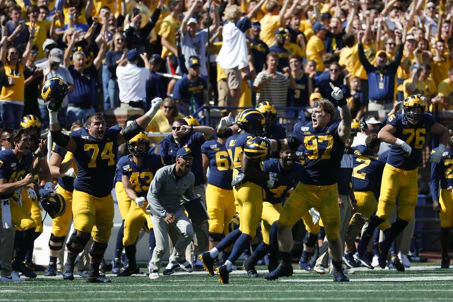 Michigan offensive lineman Ben Bredeson (74) and defensive lineman Aidan Hutchinson (97) celebrate after beating Army 24-21 in double-overtime in Ann Arbor, Mich. Photo: Paul Sancya / Associated Press