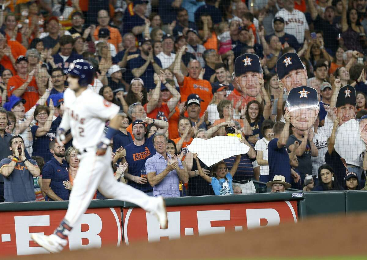Fans hold up giant faces of Houston Astros short stop Alex Bregman (2) as he makes his way around the bases after hitting a solo home run in the sixth inning against the Seattle Mariners at Minute Maid Park in Houston on Saturday, Sept. 7, 2019. Houston Astros won the game 2-1.