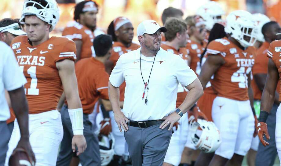 Sam Ehlinger walks nearby as coach Tom Herman gets his team ready pregame as Texas hosts LSU at Darrell K. Royal Stadium on September 7, 2019. Photo: Tom Reel, Staff / Staff Photographer / 2019 SAN ANTONIO EXPRESS-NEWS