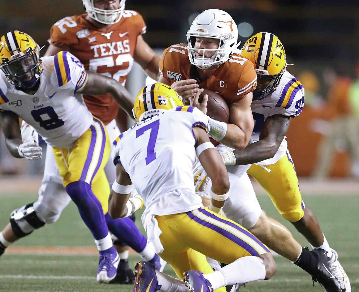 UT quarterback Sam Ehlinger gets sandwiched on a tackle in the open field. Ehlinger had a big night in a losing cause, throwing for 401 yards and four touchdowns while running for 60 yards and a score.