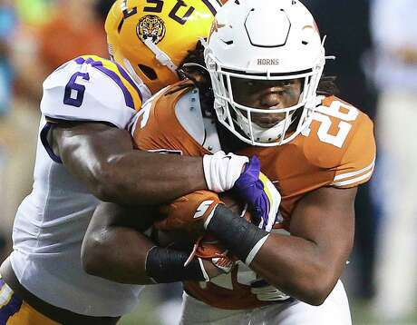 Longhorn running back Keaontay Ingram hangs on to the ball on a run in the first half as Texas hosts LSU at Darrell K. Royal Stadium on September 7, 2019.