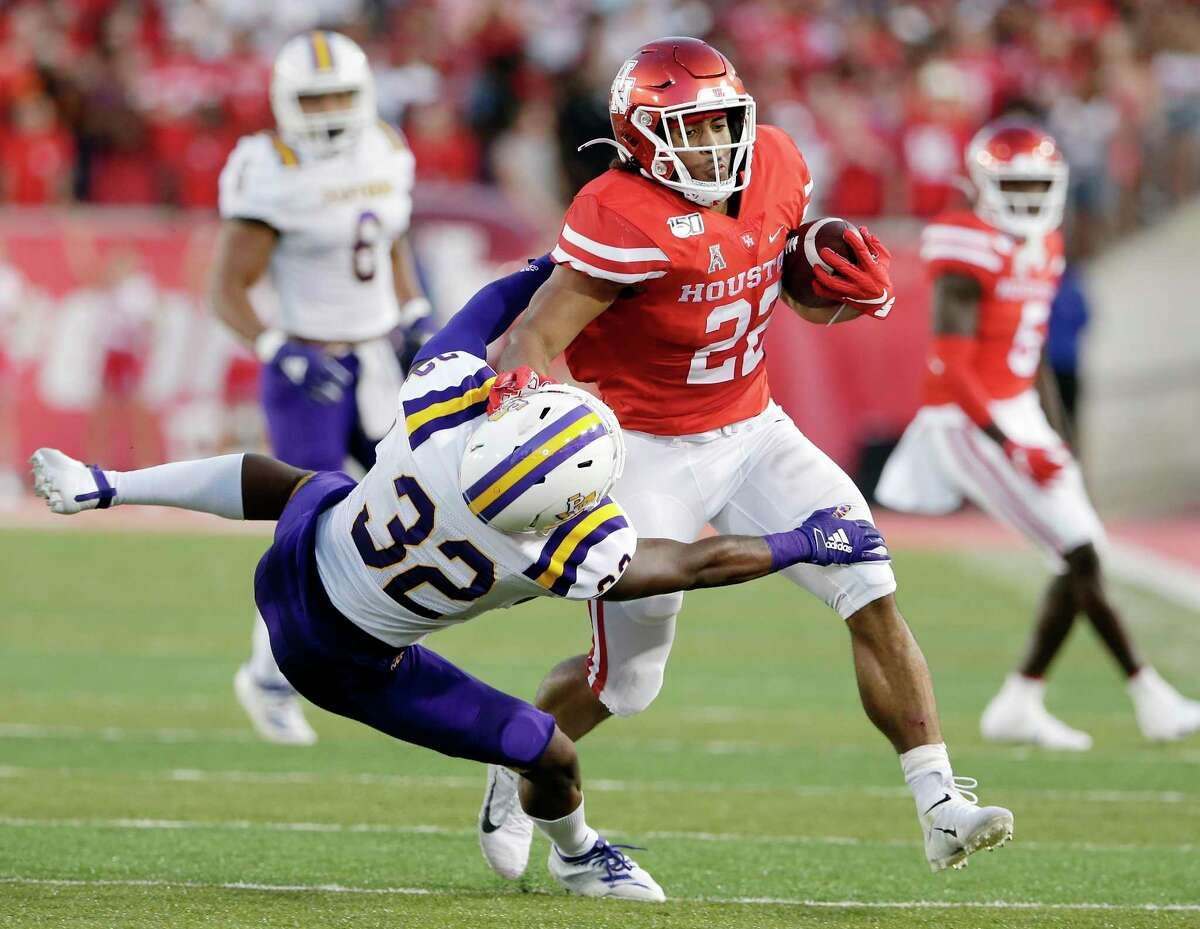 Houston running back Kyle Porter. who ran for a career-high 120 yards, bowls over Prairie View defensive back Darius Hawkins.