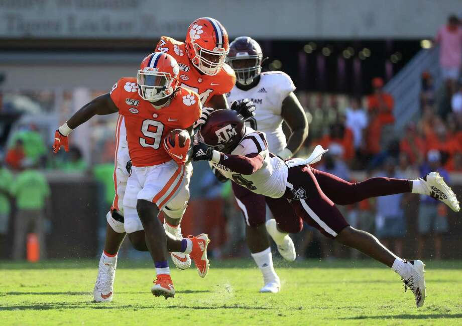 CLEMSON, SOUTH CAROLINA - SEPTEMBER 07: Keldrick Carper #14 of the Texas A&M Aggies tries to stop Travis Etienne #9 of the Clemson Tigers during their game at Memorial Stadium on September 07, 2019 in Clemson, South Carolina. (Photo by Streeter Lecka/Getty Images) Photo: Streeter Lecka / Getty Images / 2019 Getty Images