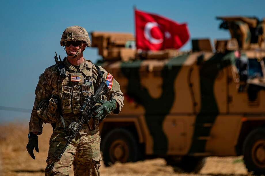 An American soldier stands guard during a patrol with Turkish troops of Tal Abyad, Syria. Photo: Delil Souleiman / AFP / Getty Images