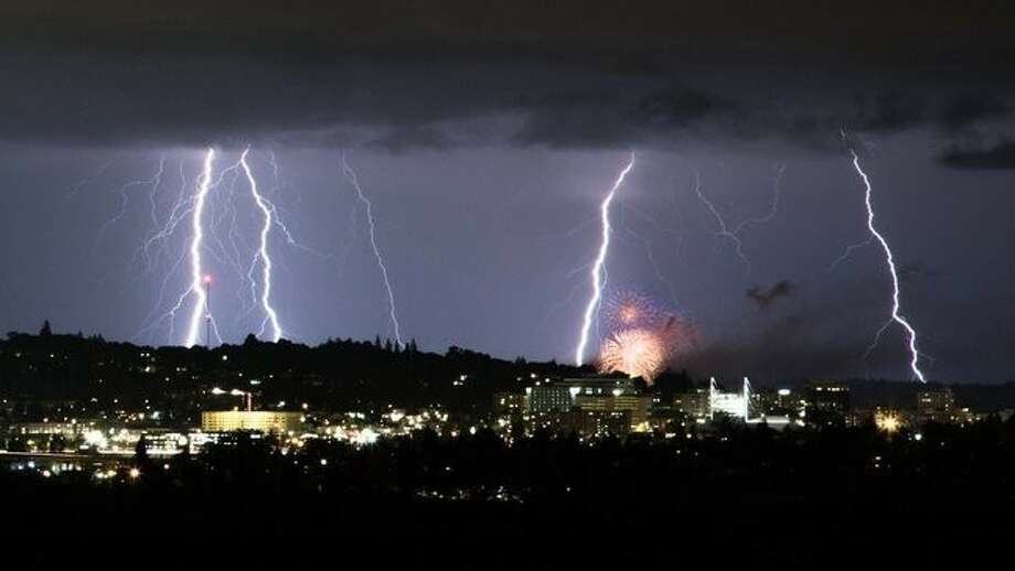 Lightning as seen from Everett as fireworks from Mukilteo go off in the foreground. Photo: Ben Jurkovich / KOMO News
