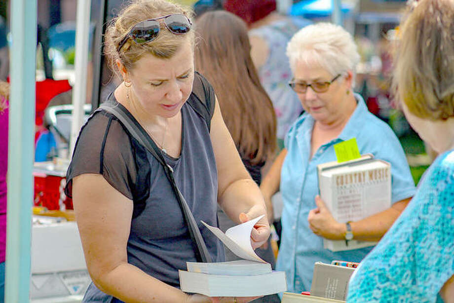 A book lover thumbs through a novel Saturday during the Edwardsville Book Festival at City Park. Photo: Andrew Malo | For The Intelligencer Photos By Andrew Malo | The Intelligencer