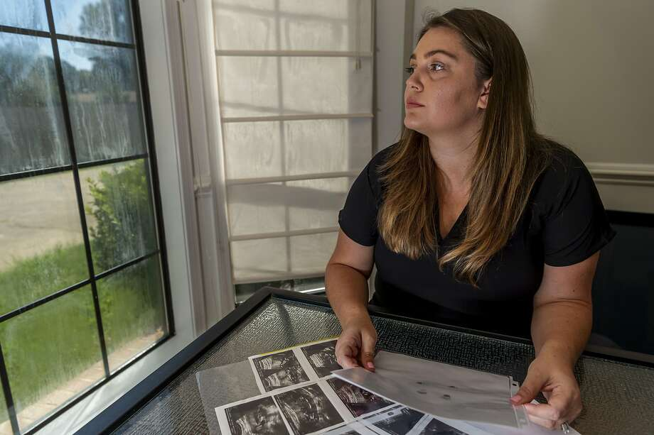 In this Aug. 29, 2019, photo, Hevan Lunsford poses for a photo with her son's ultrasounds and footprints and handprints of her son, in Prattville, Ala. Lunsford found out when she was five months pregnant that the baby she would later name Sebastian was severely underdeveloped and had only half of a heart. Lunsford said she felt the only way to guarantee her son would not suffer would be to end the pregnancy and was told she would need to travel to Georgia for the procedure. Lunsford is one of thousands of women across the U.S. in recent years who have crossed state lines for an abortion. (AP Photo/Vasha Hunt) Photo: Vasha Hunt / Associated Press