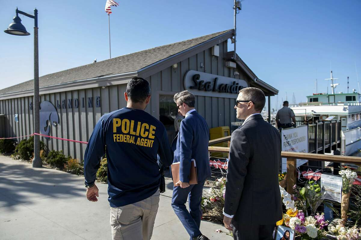 Federal agents walk past a memorial for the victims of the Conception dive boat fire on the Santa Barbara Harbor in Santa Barbara, Calif. Sunday, Sept. 8, 2019. Authorities served search warrants Sunday at the Southern California company that owned the scuba diving boat that caught fire and killed dozens of people last week. (AP Photo/Christian Monterrosa)