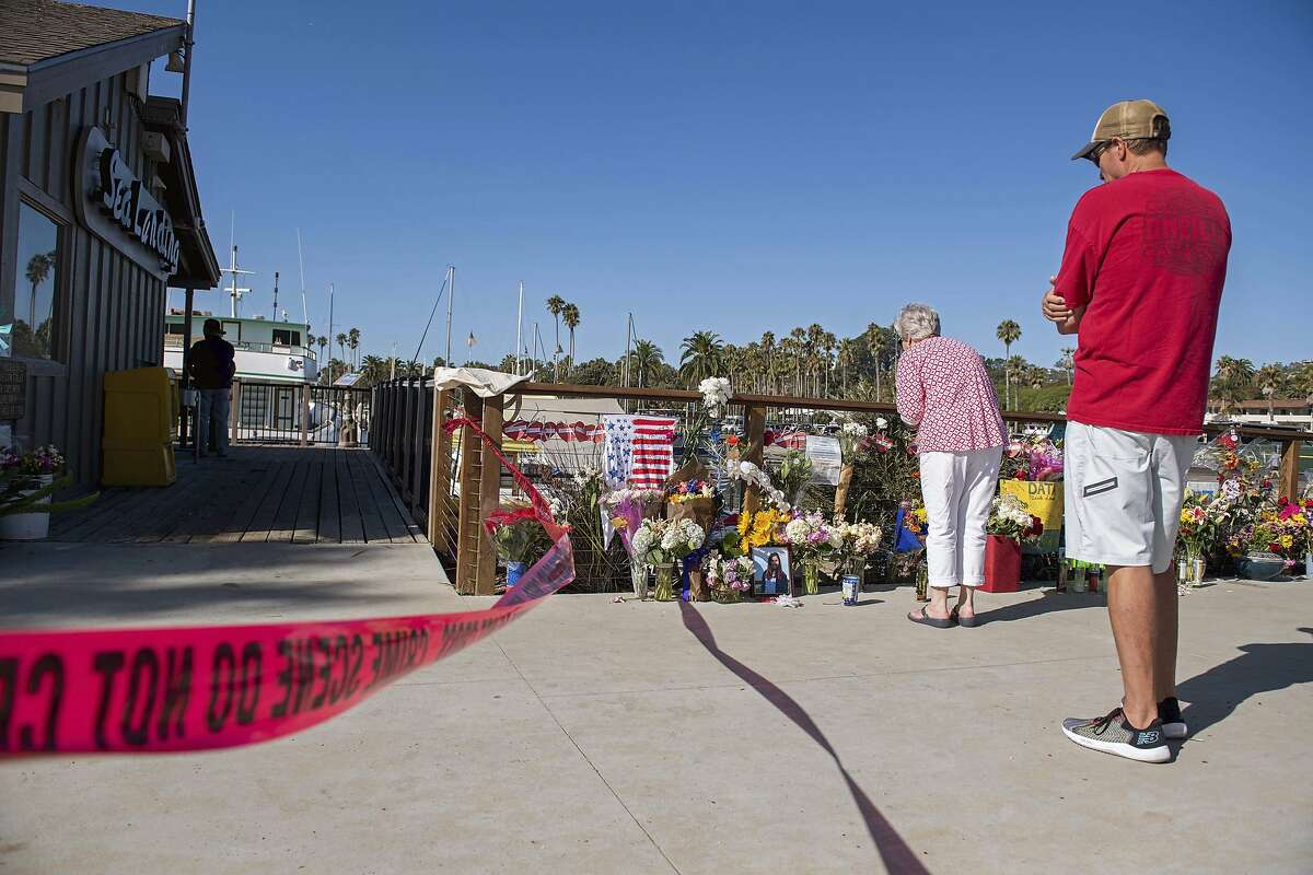 People gather around a memorial for the victims of the Conception dive boat fire as authorities search the Truth Aquatics' offices, the California company that owned the scuba diving boat that caught fire and killed dozens of people last week, on the Santa Barbara Harbor in Santa Barbara, Calif., Sunday, Sept. 8, 2019. (AP Photo/ Christian Monterrosa)