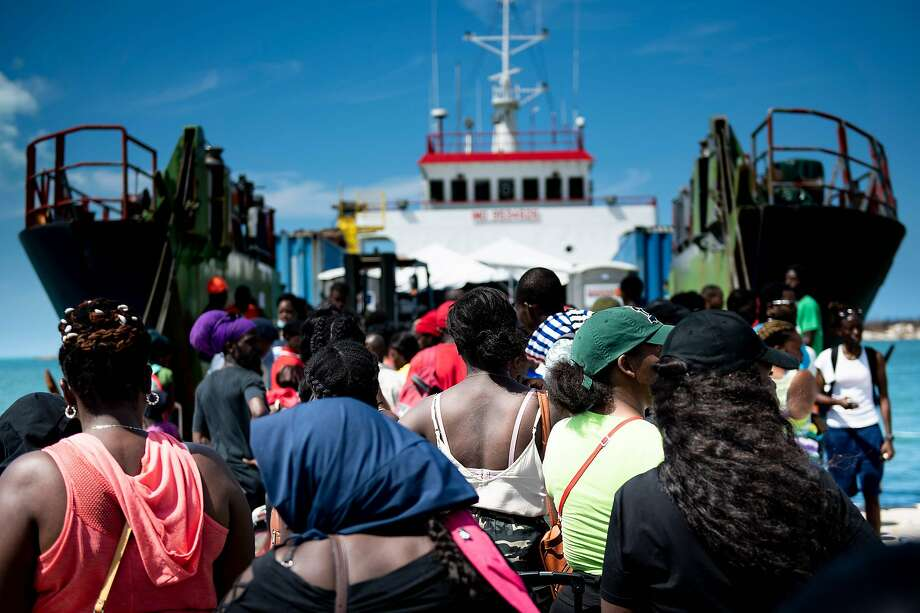 People board a cargo ship Saturday for evacuation to Nassau, Bahamas, from Abaco Island. Officials were building shelters and temporary housing for thousands of newly homeless. Photo: Brendan Smialowski / AFP / Getty Images