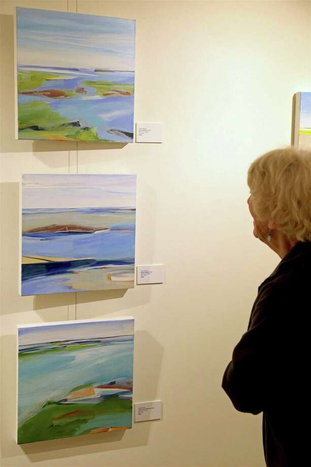 "Jane Bowler of Fairfield studies some work at the opening reception for the art show ""Coastal Expressions"" by Joyce Grasso at the Pequot Library on Thursday, Sept. 5, 2019, in Fairfield, Conn. Photo: Jarret Liotta / Jarret Liotta / ©Jarret Liotta"